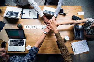 Employés se serrant la main au dessus d'une table de réunion