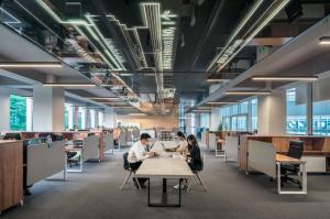 Salle de travail entreprise avec employés devant leur ordinateur