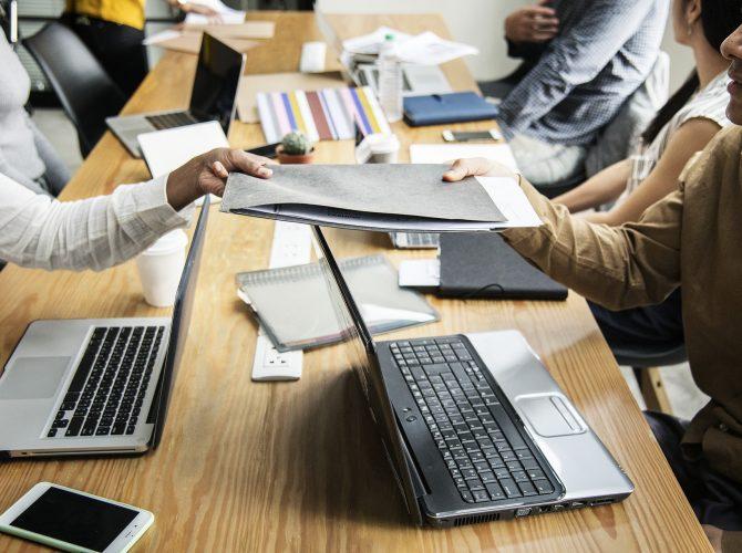 Personnes avec des ordinateurs portables assises autour d'une longue table