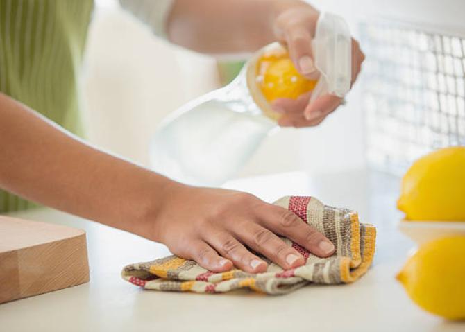 Femme qui nettoie une table avec un microfibre